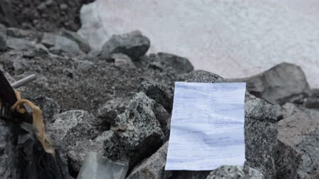 trail marker : Paper notice taken out from stony cairn on the mountain pass. Khibiny massif, Kolsky Peninsula, Russia