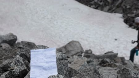 trail marker : Hand written paper note with contact information of group held mountain pass, taken out of stony cairn. Climber, rescuer goes further. Khibiny massif, Kolsky Peninsula, Russia
