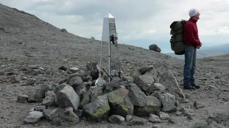 trail marker : Senior hiker with backpack standing on mountain pass near monument in honor of the lost climbers at winter hiking, South Rischorr, Khibins, Russia