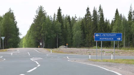 wayside : KARELIA, RUSSIA - CIRCA JUL, 2015: Auto-truck drives near road exit and direction sign on the Kola route. The Kola route is federal highway from St. Petersburg to Murmansk. Stock Footage