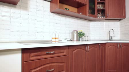 mutfak malzemesi : Brown wooden furniture and white tiles at kitchen interior after repairs