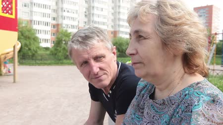 stáří : Mature couple talking together while sitting at playground and waiting their child
