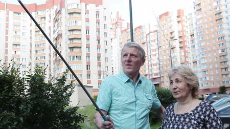 опасность : Husband and wife using selfie stick for camera beyond the normal range of the arm