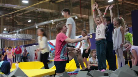парк : ST. PETERSBURG, RUSSIA - CIRCA OKT, 2015: Sport instructor helps children to jump somersault in pit with foam at kids party. The Jumping Park 1 is in city mall center Leto