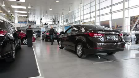 sala de exposição : ST. PETERSBURG, RUSSIA - CIRCA APR, 2015: Buyers look at vehicles standing in car dealership showroom. The Rolf Lahta is a official dealer of Hyundai