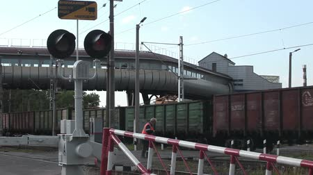 úroveň : ST. PETERSBURG, RUSSIA - CIRCA JUN, 2015: Freight train passes railway crossing with closed barriers and red traffic light. Guarded railroad crossing is in city