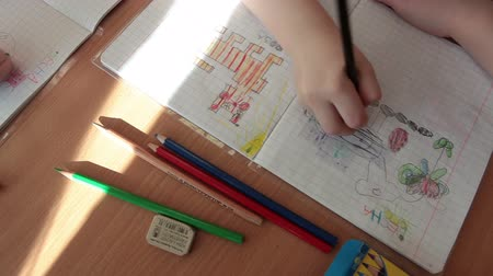 Çocuk bakımı : ST. PETERSBURG, RUSSIA - CIRCA MAY, 2015: Children drawings are on paper. Educational lesson is in classroom with kids sitting at desks. Russian daycare center for preschoolers Stok Video