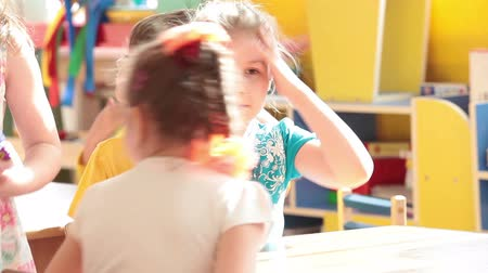 Çocuk bakımı : Young girl sitting at table with happy children. Morning at the Russian daycare center Stok Video