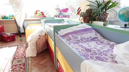 cobertor : Woman a nanny helping to prepare three-tier beds in the nursery for daytime sleeping, putting bedclothes