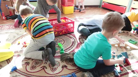 hračka : ST. PETERSBURG, RUSSIA - CIRCA MAY, 2015: Cute boys and girls have fun while playing toys on the floor of classroom. Russian daycare center for preschoolers