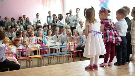 Çocuk bakımı : ST. PETERSBURG, RUSSIA - CIRCA MAY, 2015: Small children of younger group sing the song for graduating kids in nursery. Russian daycare center Stok Video