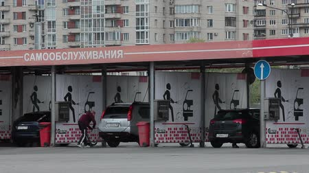 myjnia samochodowa : SAINT-PETERSBURG, RUSSIA - CIRCA JUN, 2015: Drivers wash vehicles at coin-operated multi-bay self-serve carwash. Self-service is a simple and automated type of car washautomated type of car wash