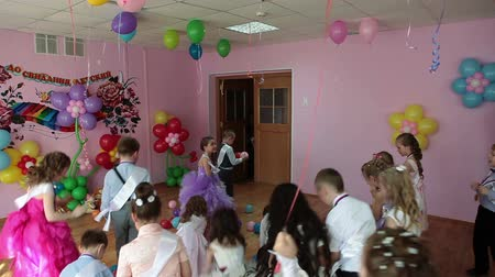 Çocuk bakımı : ST. PETERSBURG, RUSSIA - CIRCA MAY, 2015: Boys and girls have firework from air balloons at theater stage in kindergarten, Russia. Graduation party is in daycare center