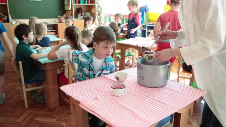 múltiplas : ST. PETERSBURG, RUSSIA - CIRCA MAY, 2015: Nanny pours beverage for kids. Preschool children have a lunch in nursery school. Russian kindergarten is a preschool educational institution Vídeos