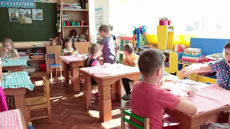 Çocuk bakımı : ST. PETERSBURG, RUSSIA - CIRCA MAY, 2015: Preschool children have a lunch in nursery school while sitting at tables. Russian kindergarten is a preschool educational institution