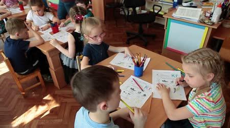 Çocuk bakımı : ST. PETERSBURG, RUSSIA - CIRCA MAY, 2015: Boys and girls a pupils sit at the desks at brain lesson in day-care center, drawing on the paper. Russian kindergarten is a preschool educational institution Stok Video