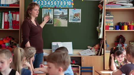 Çocuk bakımı : ST. PETERSBURG, RUSSIA - CIRCA MAY, 2015: Woman educator in daycare center teaches a class while standing near blackboard and showing pictures. Russian kindergarten is a preschool educational institution Stok Video