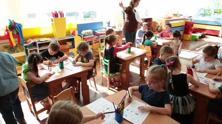 Çocuk bakımı : ST. PETERSBURG, RUSSIA - CIRCA MAY, 2015: Preschool children a pupils are on the early childhood development exercises in daycare center. Educator is at the work. Russian kindergarten is a preschool educational institution