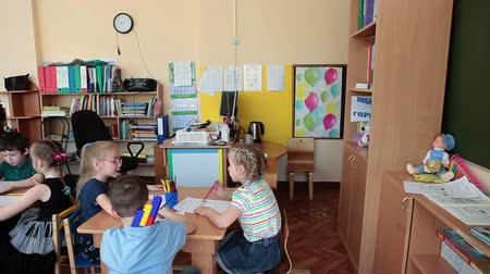 Çocuk bakımı : ST. PETERSBURG, RUSSIA - CIRCA MAY, 2015: Woman educator of day-care center helps children to paint at lesson. Russian kindergarten is a preschool educational institution