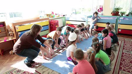 Çocuk bakımı : ST. PETERSBURG, RUSSIA - CIRCA MAY, 2015: Activities organizer plays the game with children in classrom. Russian kindergarten is a preschool educational institution Stok Video