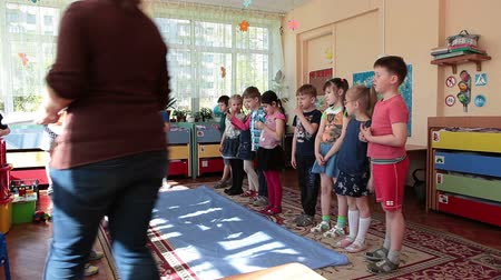 Çocuk bakımı : ST. PETERSBURG, RUSSIA - CIRCA MAY, 2015: Kids start to play games in classroom at the daycare center. Woman is a educator. Russian kindergarten is a preschool educational institution Stok Video