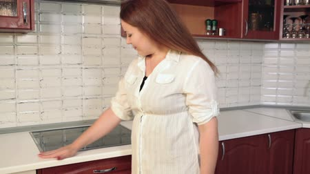 kitchen furniture : Happy housewife touching her new furniture and appliance at domestic kitchen