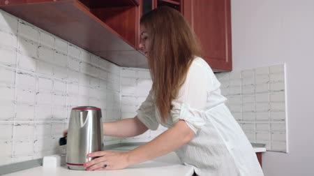 sprzataczka : Housewife putting steel electric tea kettle at the white countertop in kitchen