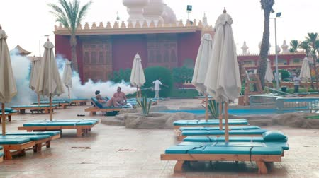 komary : HURGHADA, EGYPT - CIRCA NOV, 2015: Man uses a fogging machine for mosquitos prevent at the hotel poolside. Mosquito control for around with dispersing liquid chemicals over large areas is in resorts Wideo