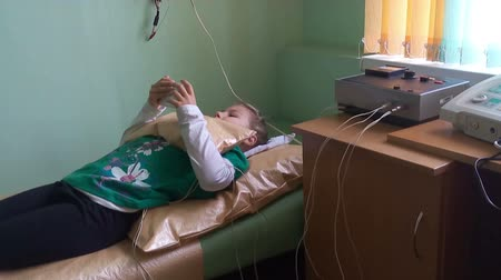 emitter : ST. PETERSBURG, RUSSIA - CIRCA OCT, 2015: Young ill child has electrophoresis procedure while lays sofa and plays mobile phone. Ambulatory treatment is in Russian childrens polyclinic center.