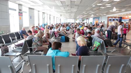 De luchthaven van Hurghada, Egypte - CIRCA november 2015: Russische passagiers zitten aan vertrekhal voor charters vliegtuigen boarding. Interieur van Hurgada International Airport Stockvideo