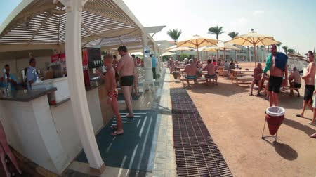 společenská místnost : HURGHADA, EGYPT - CIRCA NOV, 2015: Free fast food snacks and drinks bar for visitors is on the sandy coast line. People take beverages as soda and beer. Several spas common sand beach area Dostupné videozáznamy