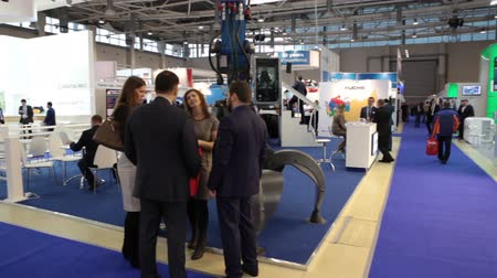 demirli : MOSCOW, RUSSIA-CIRCA DEC, 2015: Group of businesspeople stand in the hall in front of excavator machine. The Metal-Expo 2015. Metal and Steel Market, the 21st International Industrial Exhibition was in the All-Russia Exhibition Center Stok Video