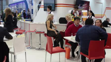 demirli : MOSCOW, RUSSIA-CIRCA DEC, 2015: Visitors and members of exhibition sit at the desk and talk ogether on the Metal-Expo 2015. Metal and Steel Market, the 21st International Industrial Exhibition was in the All-Russia Exhibition Center