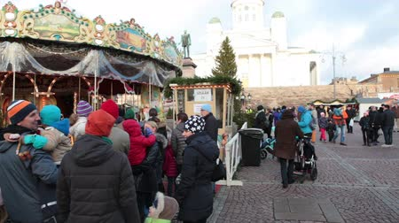 senate square : HELSINKI, FINLAND - CIRCA, DEC, 2015: Parents with children stand in queue for ride on the carousel at the fair in Christmas holidays. Senate square. Retail and entertainment annual fair is held in city Stock Footage