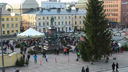 senate square : HELSINKI, FINLAND - CIRCA, DEC, 2015: Christmas green tree and trading stands are on the Senate square. Top view. People walk charity fair near the Helsinki Cathedral. It is the Finnish Evangelical Lutheran church, located in centre of city Stock Footage