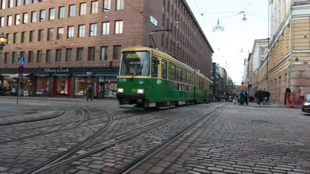 senate square : HELSINKI, FINLAND - CIRCA, DEC, 2015: Green streetcar drives on the Aleksanterinkatu street near the Senate Square in city. Public passenger ecological transport is in capital of Finland. Sound Stock Footage