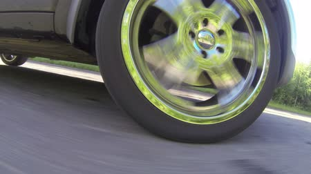 dönen : Action camera shooting of spinning car wheel when driving on country road Stok Video