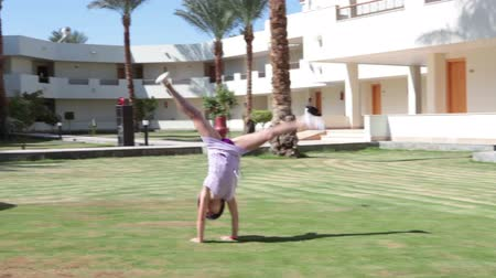 yards : Young playful girl doing a circular sideways handspring with the arms and legs extended then cross split on the green lawn