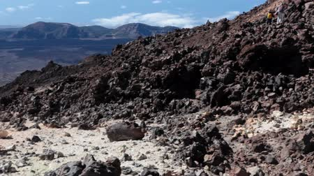 hardened lava : TEIDE, TENERIFE - CIRCA JAN, 2016: Rocky trails with volcanic formations are on southeast slope of Teide volcano. People hike at winter season. Mount Teide is the highest point in Spain and Europe