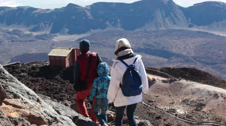 hardened lava : TEIDE, TENERIFE - CIRCA JAN, 2016: Family of three people are on the rocky path on steep southeast slope with view of upper station of cable car. Route No. 10 is trail to the crater of Teide, Spains highest peak.