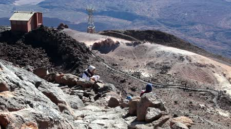hardened lava : TEIDE, TENERIFE - CIRCA JAN, 2016: Family of three people comes down the rocky path on steep southeast slope with view of upper station of cable car. Route No. 10 is trail to the crater of Teide, Spains highest peak.