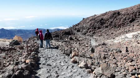 hardened lava : TEIDE, TENERIFE - CIRCA JAN, 2016: Rocky trails with volcanic formations and flows of lava are on mountainside of Teide volcano. People hike at winter season. Mount Teide is the highest point in Spain and Europe