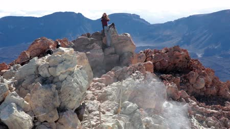 manges : TEIDE, TENERIFE, SPAIN - CIRCA JAN, 2015: People stand on the top point of Teide volcano with smoking gas from crater. Mount of Teide is popular touristic place with permit acces
