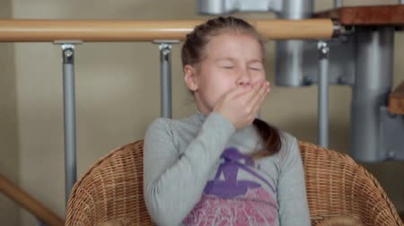 alergia : Seven-year girl sitting in the chair and sneezing, covering her mouth with her hands