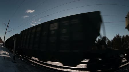 napos : Sun shining through the driving freight cars of train at winter sunny day, wide angle close-up view. Loopable