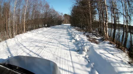 vista frontal : Car driving through the sunny winter forest at snowy bad road, front outdoor view