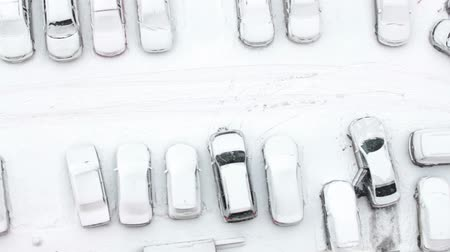 множество : Man driver parks the vehicle on the snow-covered parking lot in the building yard, top view. Winter in Russia