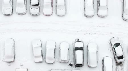 winter place : Man driver close the door of his vehicle on the snow-covered parking lot in the building inner yard, top view. Winter in Russia Stock Footage
