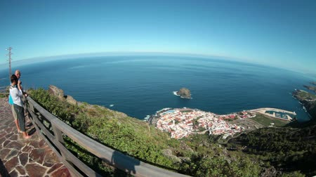 platform edge : GARACHICO, TENERIFE, SPAIN-CIRCA JAN, 2016: People stand on the Mirador (viewpoint) and look at beautiful view of cape with Garachico town. Northern part of Tenerife island. Wide angle Stock Footage