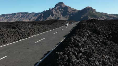 hardened lava : TENERIFE, SPAIN - CIRCA JAN, 2016: Cars drive on lifeless fields with lava pebbles of route TF-38. National park Teno is in central part of Tenerife Island, Canary, Spain